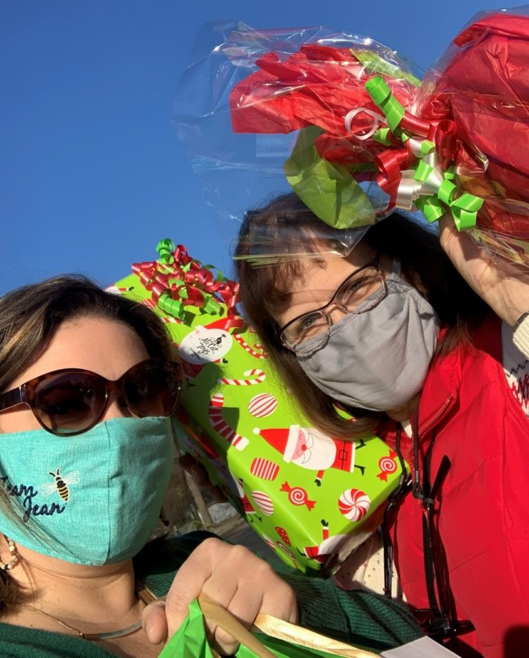 Two women wearing glasses and pandemic face masks holding brightly wrapped holiday gifts.