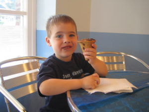 Child eating chocolate ice cream cone at a silver table with a blue wall background.