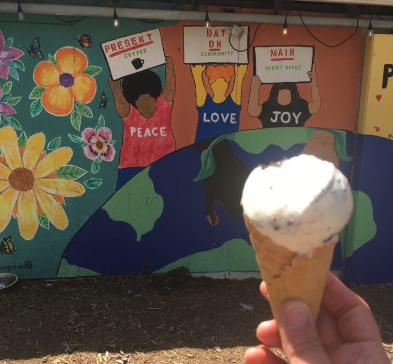 Wall mural of people, flowers, the earth at Present Day on Main in Carrboro with an ice cream cone in the foreground.