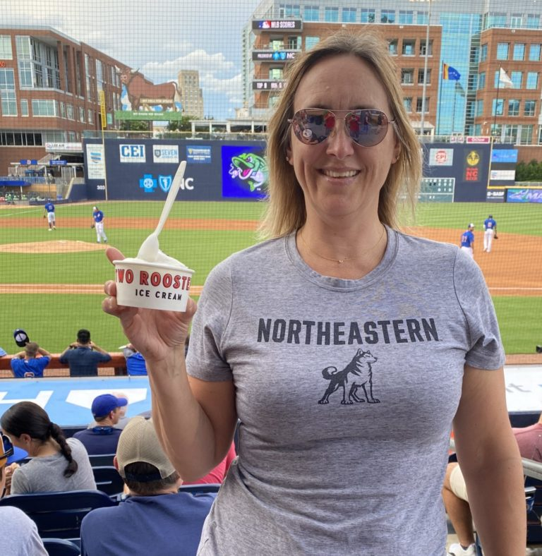 Author holding cup of Two Rooster ice cream with Durham Bulls field/park in the backgroud.