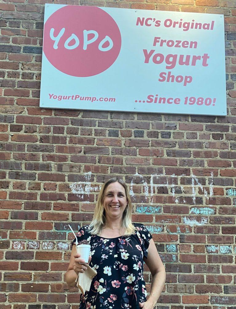 Author standing under a Yogurt Pump of Chapel Hill sign against a brick wall holding a cup of frozen yogurt.