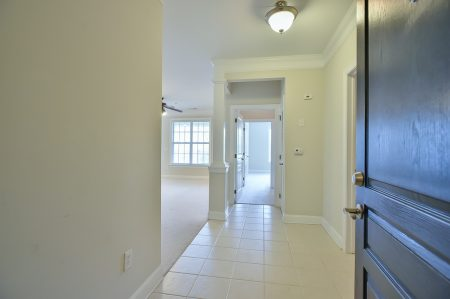 Empty foyer with white tile floor and beige walls.