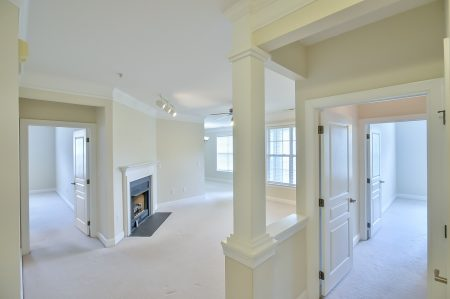 View from entry into empty living room with large column and fireplace, and empty bedrooms, all with beige carpet and walls.