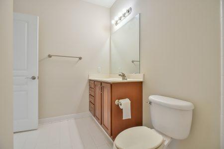 Bathroom with wood vanity, toilet and white tile floor.