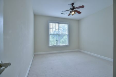 Empty bedroom with window, ceiling fan and beige walls and carpet.