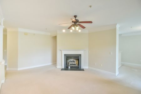Empty living room with fireplace, ceiling fan, beige carpet and walls.