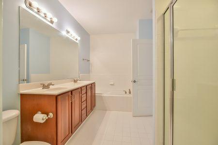 Bathroom with wood double vanity, bathtub, shower and white tile floor.