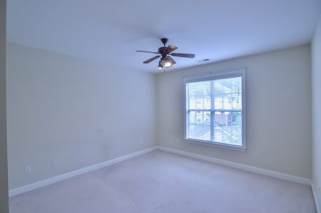 Empty bedroom with window, ceiling fan, and beige walls and carpet.
