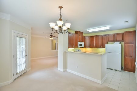 View from dining area into kitchen with brown cabinetry and into living area, all with beige walls and carpet.