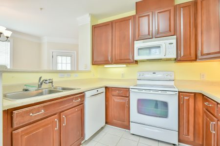 Kitchen with wood cabinetry and light yellow counter and walls with white appliances.