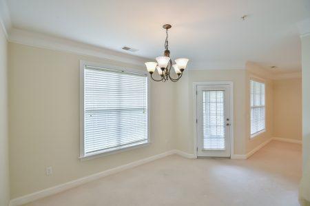 Empty dining room, beige walls and carpet. Chandelier.