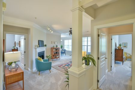 View from the door of living room with large column, entry to bedrooms and dining room