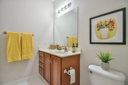 Bathroom with wood vanity, yellow towels and a plant.