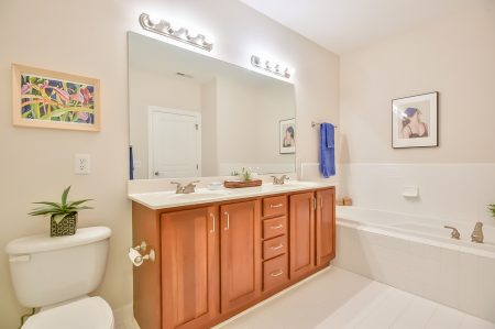 Bathroom with wood double vanity, large tub and blue towels.
