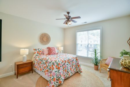Bedroom with bright colored orange bedding, mid century style dresser and nightstand and round sisal rug.