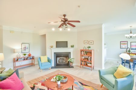 Living room with fireplace, turquoise mid centry chairs with yellow pillows, round wooden coffee table, and bright colored area rug and pillows.