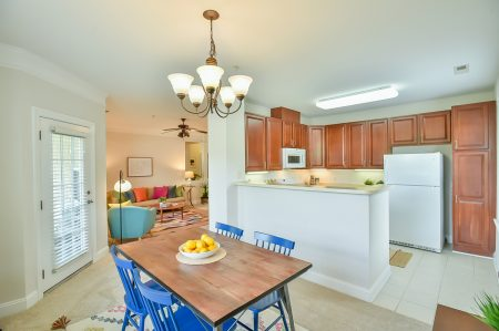 View of kitchen with wooden cabinetry, open to dining area with wood table and blue chairs open to living area with couch and colorful pillows.