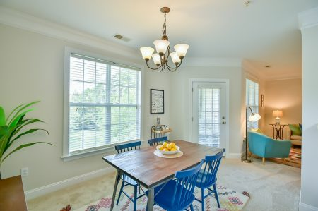 Dining area with double window and exterior windowed door, wooden table with blue chairs and chandelier.